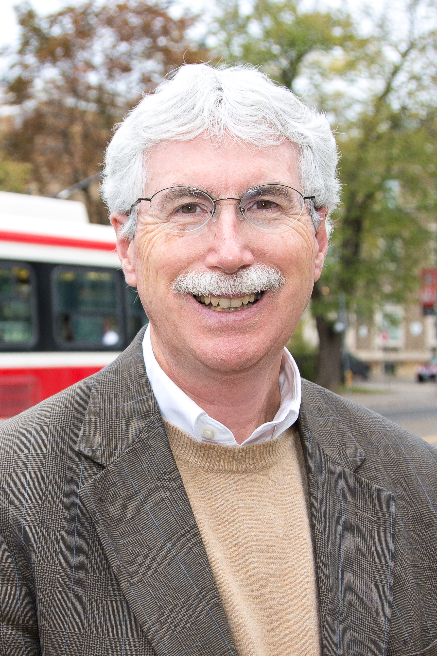 Outdoor head shot of Eric J. Miller with streetscape behind him